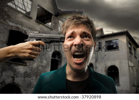 hand pointing gun at the head of man - stock photo