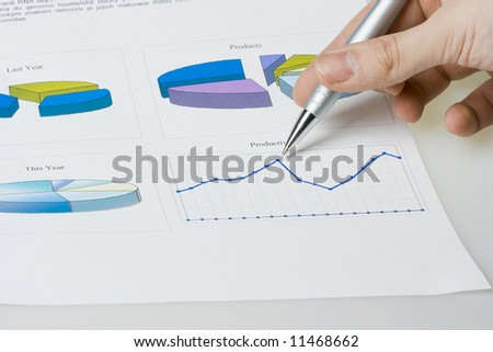 hand pointing on report with diagrams - stock photo