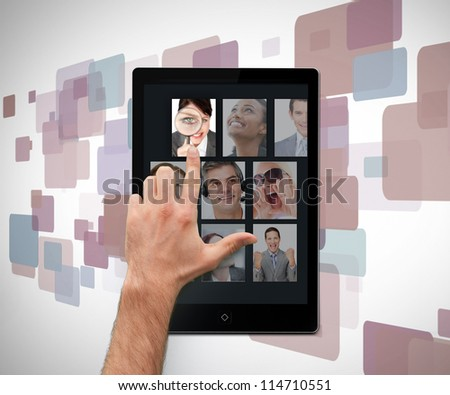 Hand pointing on tablet pc showing photos on digital background - stock photo