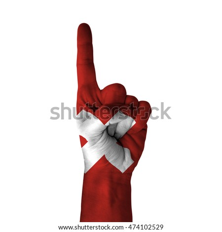 Hand pointing thumb up direction, switzerland painted with flag as symbol of up direction, first and number one symbol - isolated on white background