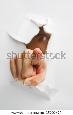 Hand pointing to camera came from cracked wall with eye gazing - one of the breakthrough series - stock photo