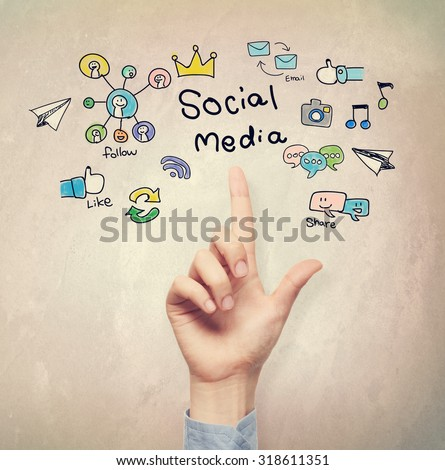 Hand pointing to Social Media concept on light brown wall background - stock photo