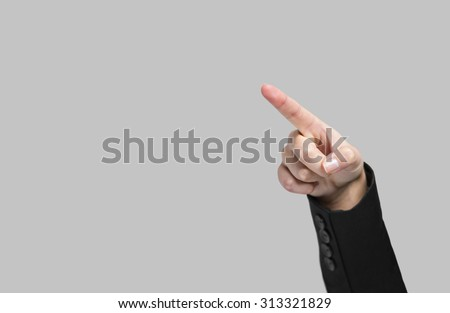 Hand pointing to the air on a grey background  - stock photo