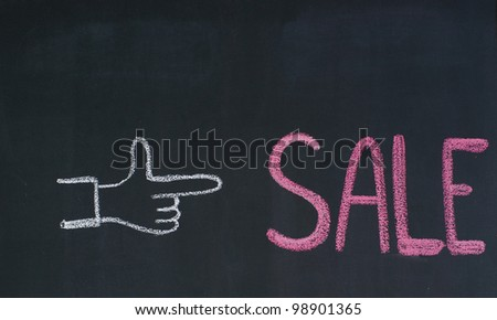 Hand pointing to the word Sale, written on a blackboard - stock photo