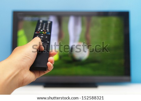 Hand pointing tv remote control towards the television as background