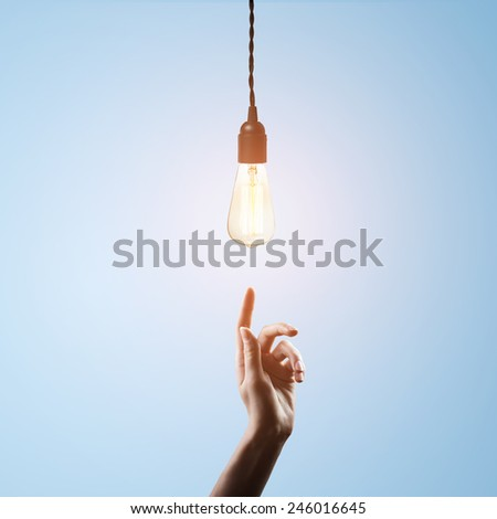 hand points to  light bulb - stock photo