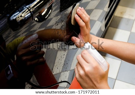 Hand polishing by clay bar and clay  lubricant for remove dirt on car surface in car-wash shop  - stock photo