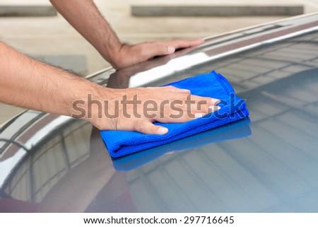 Hand polishing car bonnet with microfiber cloth - stock photo