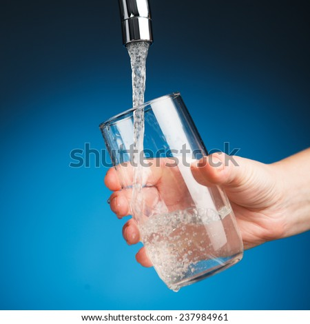 hand pouring a glass of water from filter tap - stock photo