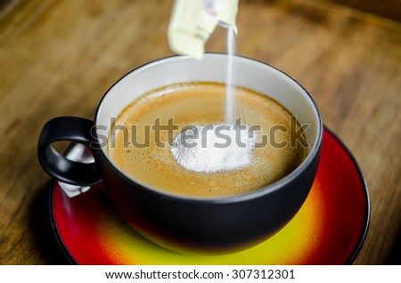 Hand pouring creamer in to a cup of coffee on wooden background. - stock photo