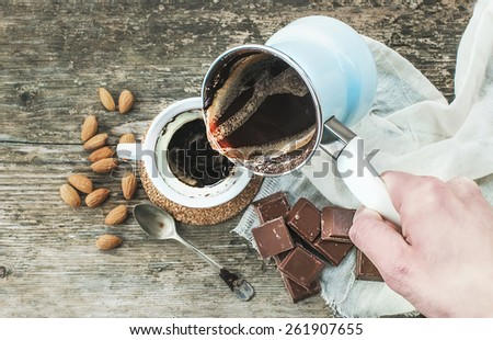 Hand pouring freshly brewed coffee from cezve (coffee pot) to a cup. Roasted almonds, a spoon, a towel, chocolate bar pieces and rough wooden desk at the background. Top view - stock photo