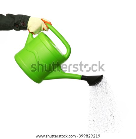 Hand pouring from green plastic watering can, isolated on white - stock photo