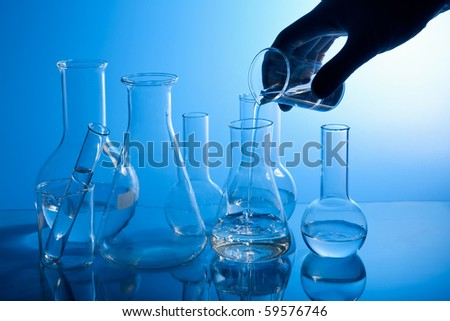 hand pouring liquid into flask - stock photo
