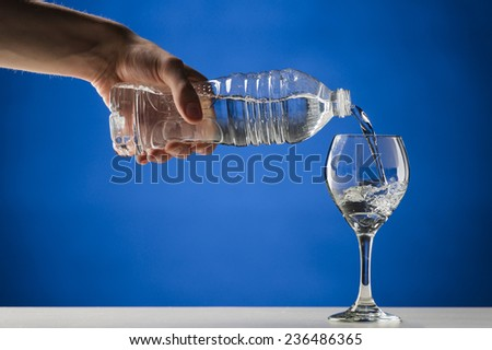 Hand pouring pure fresh water from a plastic bottle into a crystal clean stemmed glass on a white table, close-up, on blue background - stock photo