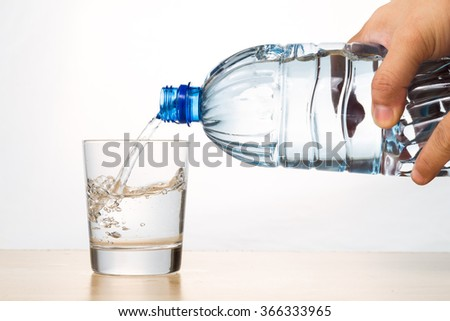 Hand pouring refreshing natural mineral water from bottle into transparent glass in white background - stock photo