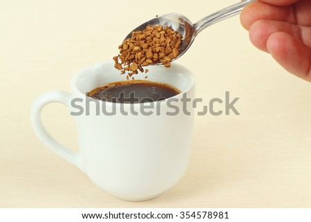 Hand pours granulated coffee from a spoon in a coffee cup - stock photo