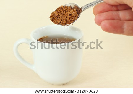 Hand pours instant coffee from a spoon in a coffee cup - stock photo