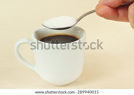 Hand pours sugar from a spoon in a coffee cup - stock photo