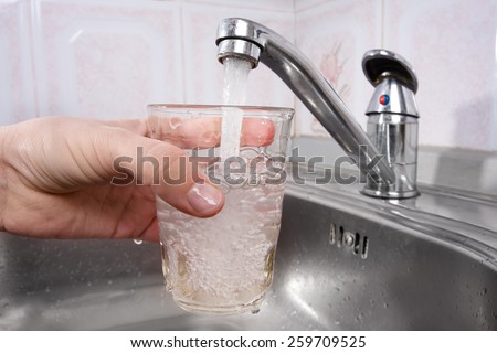 hand pours water into a glass from  faucet - stock photo