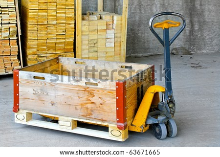 Hand powered pallet jack with wooden box - stock photo