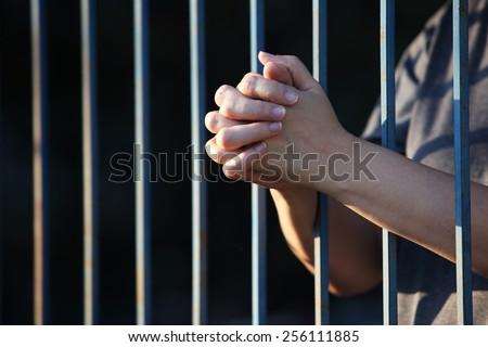 hand praying in jail - stock photo