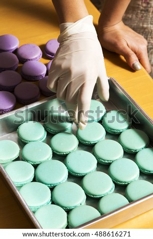Hand preparing macaroons in tray