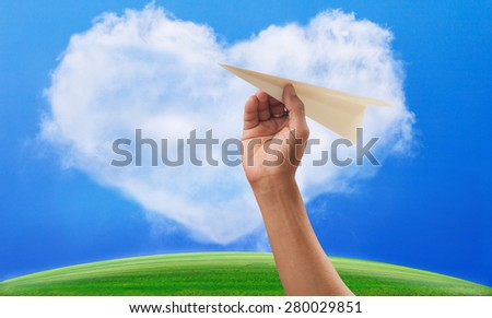 hand preparing to throwing paper plane to mid air against green grass field and heart shape white clouds on clear blue sky