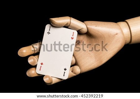 Hand presents a playing card absurd game. Heart, clover, tile, dive on the same map. Isolated on black background. With copy space text.