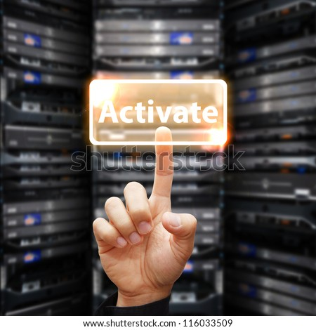 Hand press on Activate button in data center room - stock photo