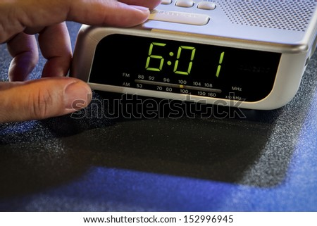 Hand press the stop button of the digital alarm clock. - stock photo