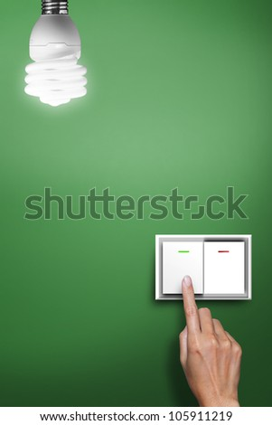 hand pressed to switch to turn on the light with green background - stock photo