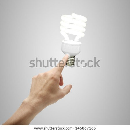 hand presses energy saving lamp on a gray background