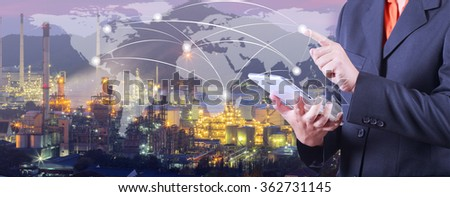 hand presses on world map with digital tablet,Industrial oil refinary  background (Elements of this image furnished by NASA) - stock photo