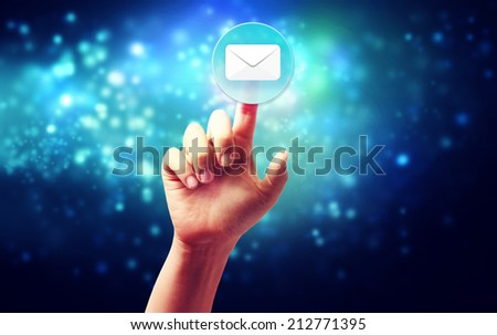 Hand pressing a envelope icon over technology blue background - stock photo