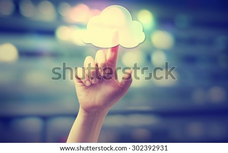 Hand pressing an cloud computing icon on blurred cityscape background - stock photo