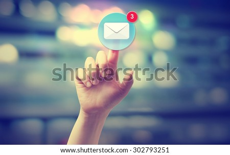 Hand pressing an email icon on blurred cityscape background  - stock photo