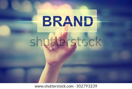 Hand pressing BRAND button on blurred cityscape background - stock photo