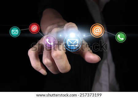 Hand pressing contact us button on the virtual screen - stock photo
