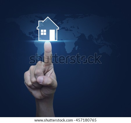 Hand pressing house icon with copy space over digital world map blue background, Real estate concept, Elements of this image furnished by NASA