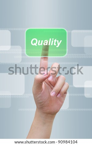 hand pressing quality button on a touch screen interface - stock photo
