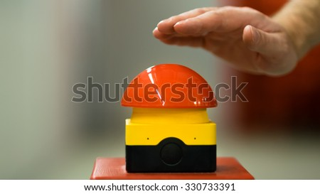 Hand pressing red emergency button - stock photo
