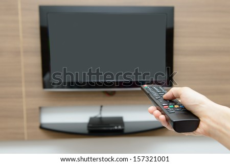 Hand pressing remote control wih TV as background - stock photo