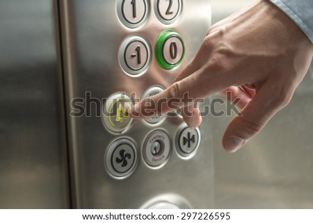 Hand pressing the alarm button in the elevator - stock photo