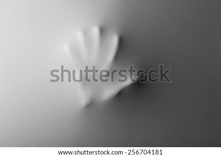 Hand pressing through fabric as horror background - stock photo