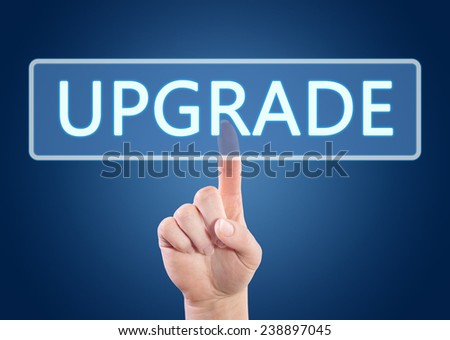 Hand pressing Upgrade button on interface with blue background. - stock photo
