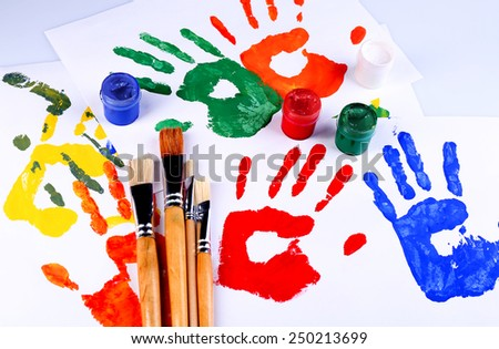 Hand prints of paint, paints and brushes on white background - stock photo