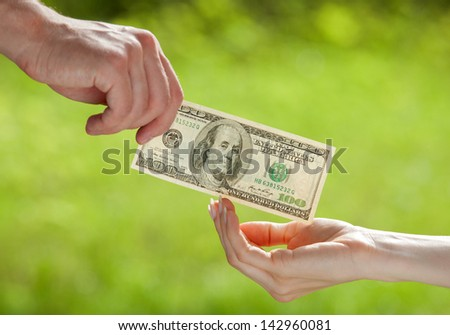Hand proposing dollar banknote to the other hand, light green background