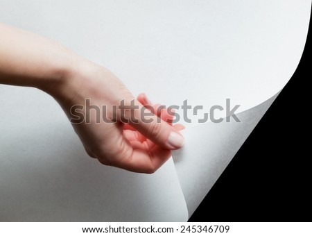 Hand pulling a bottom paper corner to uncover, reveal something. Page curl, conceptual. - stock photo