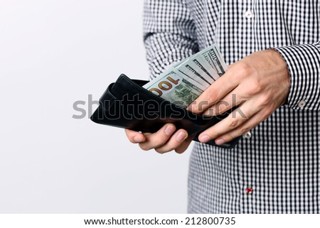 Hand pulling 100 dollars banknotes from wallet - stock photo