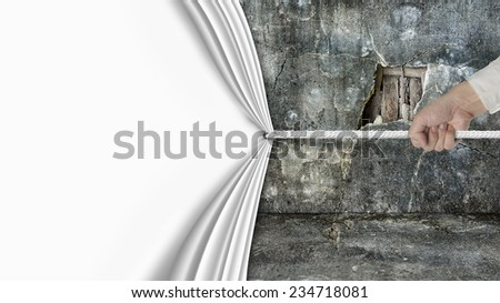 hand pulling open blank curtain covered old broken wall ruins isolated on white white background - stock photo